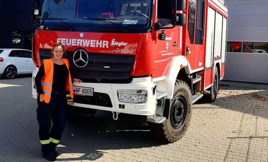 Produktmanagerin Desiree Fuhs vor einem Feuerwehrauto